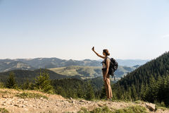 Le jeune randonneur féminin utilise le téléphone portable pour l'autoportrait dans le secteur de montagne rural des montagnes car Photographie stock libre de droits