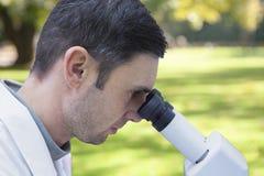 Le jeune scientifique masculin travaille avec un microscope dans un laboratoire de science images stock