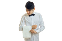 Le jeune serveur attirant se tient dans une tête de recourbement de chemise blanche et garde en main une serviette Photo stock