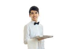Le jeune serveur de sourire attirant regarde l'appareil-photo et tenir un plateau avec une serviette Image stock