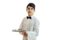 Le jeune serveur remarquable regarde loin souriant et tenant un plateau de nourriture et une serviette Photo libre de droits