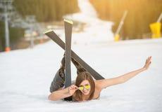 Le jeune skieur féminin nu heureux se trouve sur la pente neigeuse près du remonte-pente à la station de sports d'hiver Photo libre de droits