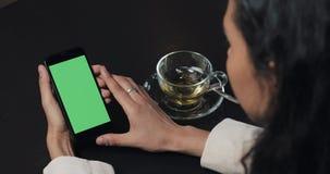 Le jeune smarthpone d'utilisation de femme d'affaires avec greenscreen le touchpad et la fin de faire des gestes en café Particip banque de vidéos
