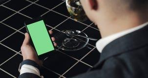Le jeune smarthpone d'utilisation d'homme d'affaires avec greenscreen le touchpad et la fin de faire des gestes en café Participa banque de vidéos