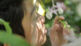 Le jeune souriant et riant le garçon asiatique d'enfant apprécie l'odeur de la floraison blanche d'orchidée clips vidéos