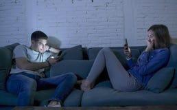 Le jeune sourire de divan de sofa de couples à la maison heureux ensemble mais séparé s'ignorant s'est concentré au téléphone por Photographie stock libre de droits