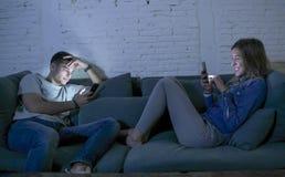 Le jeune sourire de divan de sofa de couples à la maison heureux ensemble mais séparé s'ignorant s'est concentré au téléphone por Image stock