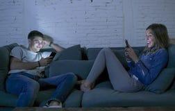 Le jeune sourire de divan de sofa de couples à la maison heureux ensemble mais séparé s'ignorant s'est concentré au téléphone por Photos libres de droits