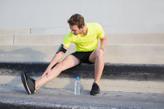 Le jeune sportif faisant la pause après obtiennent blessé au milieu de l'extérieur courant de matin de la ville Images stock