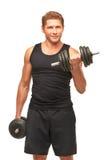 Le jeune sportif pompant le biceps muscles avec les haltères noires Images stock