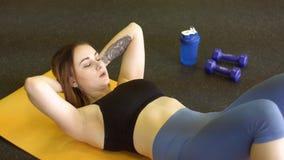 Le jeune sportwoman se trouve sur le tapis d'exercice de yellowe et fait reposer-UPS dans le centre de fitness clips vidéos