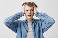 Le jeune stressant avec des mains dans les cheveux justes a le mal de tête, serre les dents avec douleur, les vies dans la tensio Photo stock