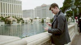 Le jeune touriste achète quelque chose au-dessus de l'Internet devant l'hôtel de Bellagio Photos stock