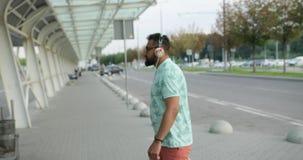 Le jeune touriste africain attirant dans les heaphones marche à l'aéroport pour un vol Il tire ses bagages 4K banque de vidéos