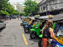 le jeune touriste féminin parle avec un conducteur automatique de pousse-pousse photos stock