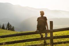 Le jeune touriste masculin avec le sac à dos s'assied sur la barrière dans vue appréciante latérale de colline la belle des monta Images stock