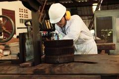 Le jeune travailleur asiatique professionnel dans l'uniforme blanc et le dispositif de protection coupant un morceau de bois sur  Photo stock