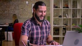 Le jeune travailleur créatif heureux avec la barbe noire gentille s'assied au bureau et a le faire appel visuel à l'ordinateur po banque de vidéos