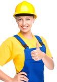 Le jeune travailleur de la construction montre le pouce vers le haut du signe Image libre de droits