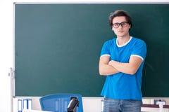 Le jeune ?tudiant masculin dans la salle de classe photographie stock