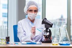 Le jeune étudiant travaillant avec les solutions chimiques dans le laboratoire Image stock
