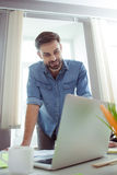 Le jeune type attirant travaille sur l'ordinateur Photographie stock libre de droits