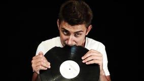Le jeune type aux cheveux courts attirant crache rapièce du disque vinyle cassé banque de vidéos