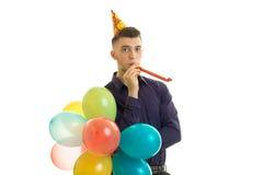 Le jeune type avec du charme drôle tient dans sa main beaucoup de ballon à air chaud Image stock