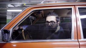 Le jeune type barbu avec de longs cheveux foncés ouvre la fenêtre de voiture rouge et les regards hors de elle banque de vidéos