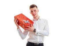 Le jeune type beau dans une chemise a augmenté dans les mains de grands boîte-cadeau Image libre de droits