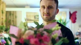 Le jeune type beau dans une veste noire tient un bouquet des fleurs banque de vidéos