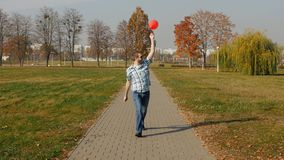 Le jeune type caucasien à la mode court avec un ballon rouge et se réjouit en nature, lent-MOIS banque de vidéos