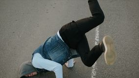 Le jeune type caucasien moderne dansant la coupure inf?rieure sur la route goudronn?e avec les taches blanches, ex?cute un appui  clips vidéos
