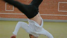 Le jeune type caucasien moderne ex?cute les tours acrobatiques, ?l?ments complexes sur la rue sur le terrain de jeu banque de vidéos