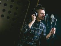 Le jeune type chantant dans le studio d'enregistrement photographie stock libre de droits