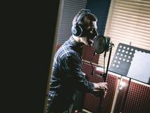 Le jeune type chantant dans le studio d'enregistrement image stock