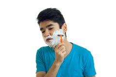 Le jeune type d'une chevelure noir a abaissé sa tête vers le bas et rase sa barbe avec un rasoir Photographie stock libre de droits