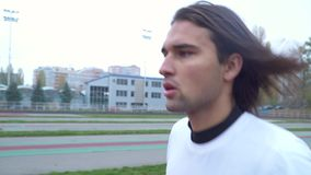 Le jeune type dans des courses d'un T-shirt de sports dans le type beau de stade avec l'extérieur pulsant de cheveux foncés folât banque de vidéos