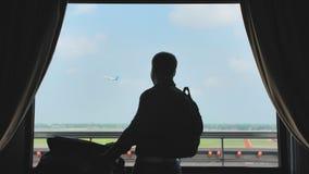 Le jeune type dans la chambre d'hôtel à l'aéroport emballe négligemment une valise avec des choses et des feuilles pour le débarq clips vidéos