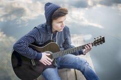 Le jeune type dans un capot joue la guitare sur le pont le soir contre le contexte d'un coucher du soleil sur la rivière Image libre de droits