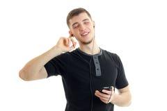 Le jeune type de sourire écoute la musique avec des écouteurs avec les yeux fermés Photos libres de droits