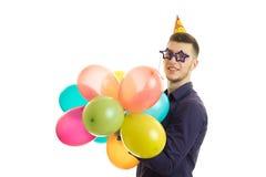 Le jeune type drôle en verres sous forme d'étoiles tient l'anniversaire de boules Photographie stock libre de droits