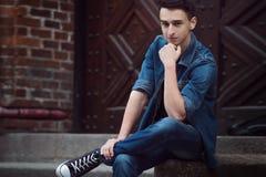 Le jeune type en denim, promenades sur la rue, s'asseyent photographie stock