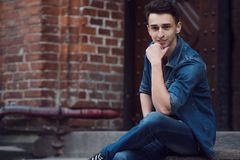 Le jeune type en denim, promenades sur la rue, s'asseyent photo libre de droits