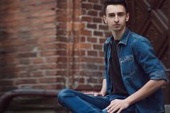 Le jeune type en denim, promenades sur la rue, s'asseyent image stock