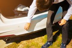 Le jeune type essuie la boue de la voiture de butoir photo libre de droits