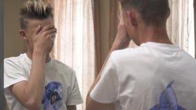 Le jeune type essuie son visage devant un miroir banque de vidéos