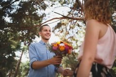 Le jeune type est apporte des fleurs à son amie à la fille de la forêt A avec une bicyclette prend des fleurs d'un type dans les  Photos stock