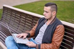 Le jeune type est indépendant travaillant sur l'ordinateur sur la rue photographie stock