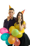 Le jeune type et la jolie fille soufflent des klaxons et des ballons colorés de transport Photo stock